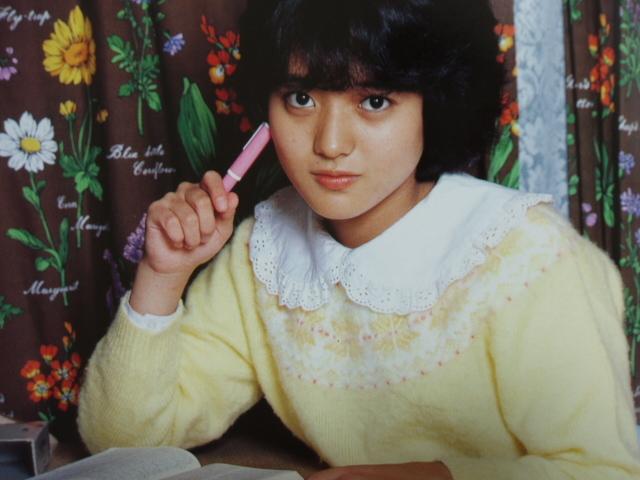 黄色のセーター姿にピンクのペンを持つアイドル時代の三田寛子